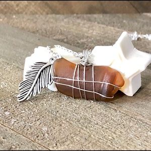 Brown sea glass pendant necklace with carved leaf